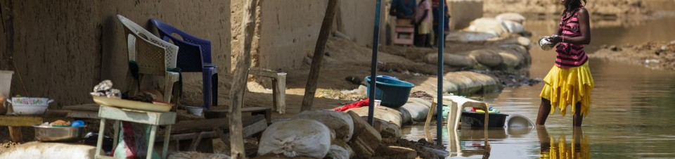 A woman cleans dishes as she stands in water in a flooded area outside her home in the Walia neighborhood of N'Djamena.