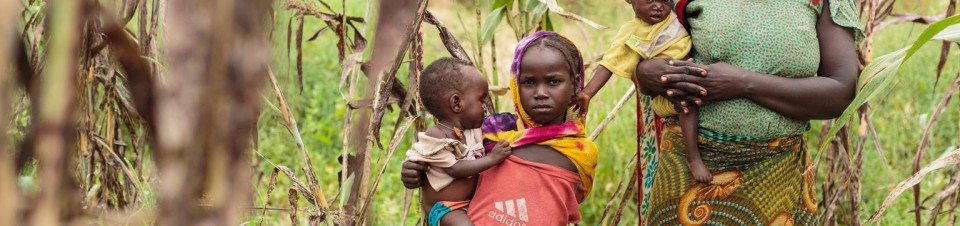 Mariam, 15, and Aljema, 8, carrying their 10-month-old twin sisters Fatouma and Toma (not visible) in sling pouches, make their way home to the village of Banala.