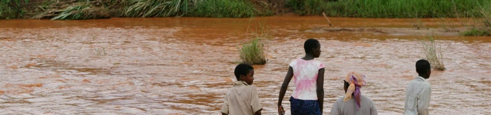 A group of displaced persons crosses a muddy and crocodile-infested river on the way to a settlement in the village of Nyamukwara near the Mozambican border.