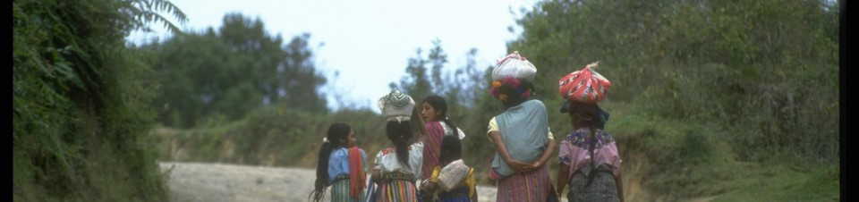 1993. After market day in the village of Santa Clara La Laguna, girls and women of the Quiche indigenous group walk up a dirt road to their mountain homes.